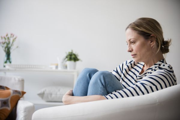 Woman on white couch holding her knees