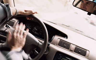 Man honking horn on motorway with frustrated expression (blurred motio
