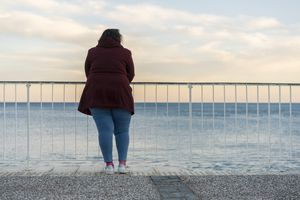woman in a red jacket stands at a fence over looking the ocean