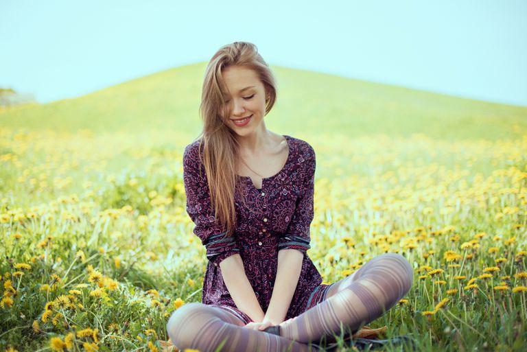 Smiling woman on dandelion meadow