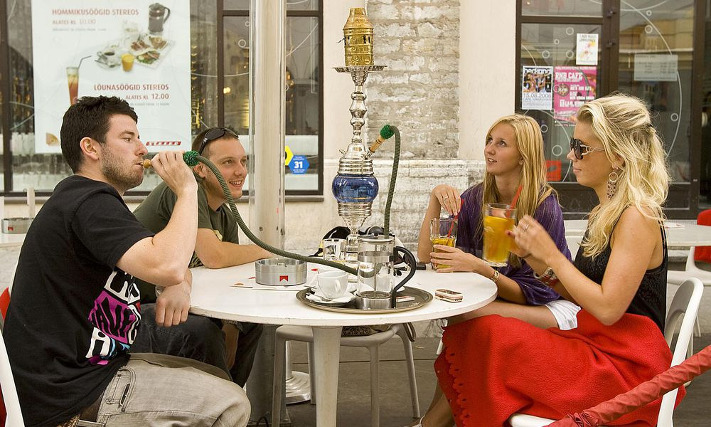 Group of people smoking hookah at an outdoor cafe.