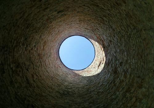 Directly Below Shot Of Sky Seen Through Well
