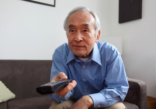 Middle-aged man seated on a couch flipping through television channels