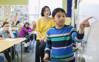 boy working with teacher on whiteboard in classroom