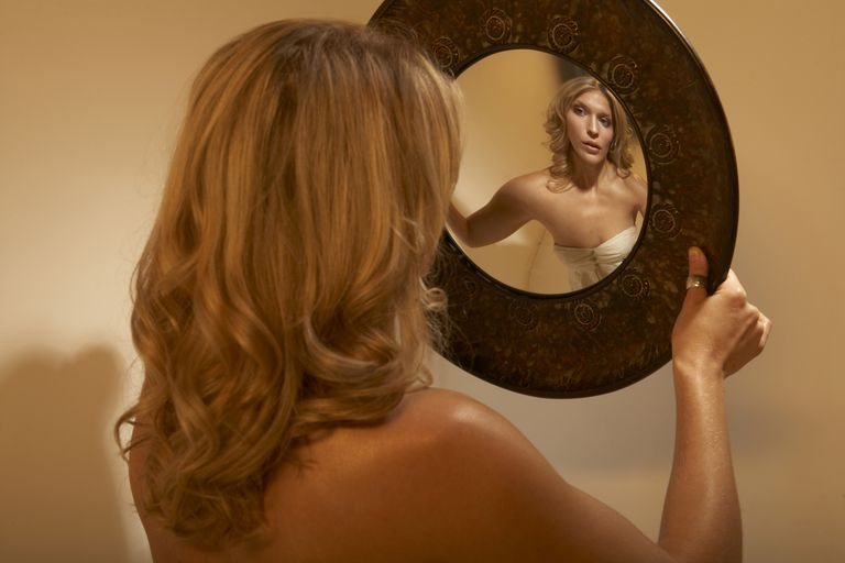 woman looking into distorted mirror