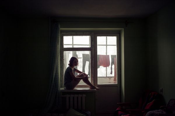 depressed woman sitting in windowsill
