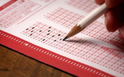 person filling out answer bubbles in multiple choice exam sheet