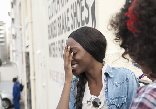 Embarrassed, smiling woman covering her face while talking to another woman