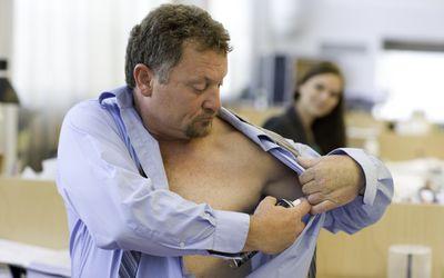 Mature man applying deodorant in office