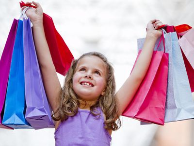 A picture of a child holding up shopping bags