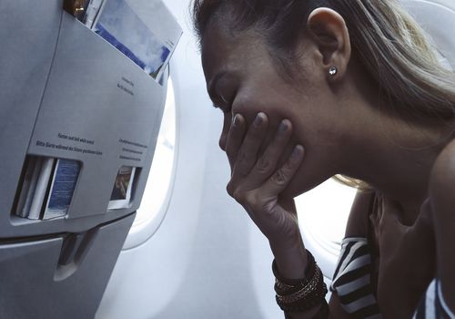 Upset woman, covering her mouth and leaning forward in airplane seat