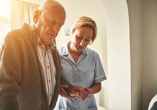 Nurse helping a senior man walk
