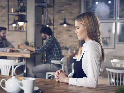Woman standing at coffee shop counter alone.