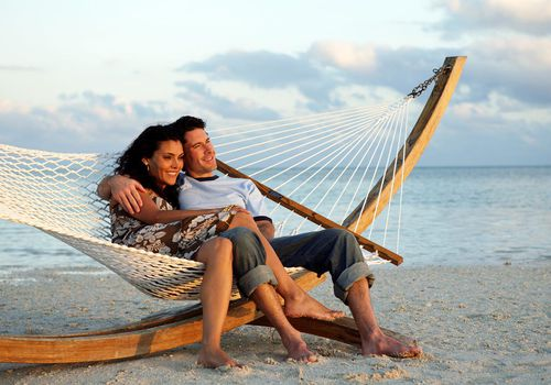 Couple relaxing in a hammock on a beach
