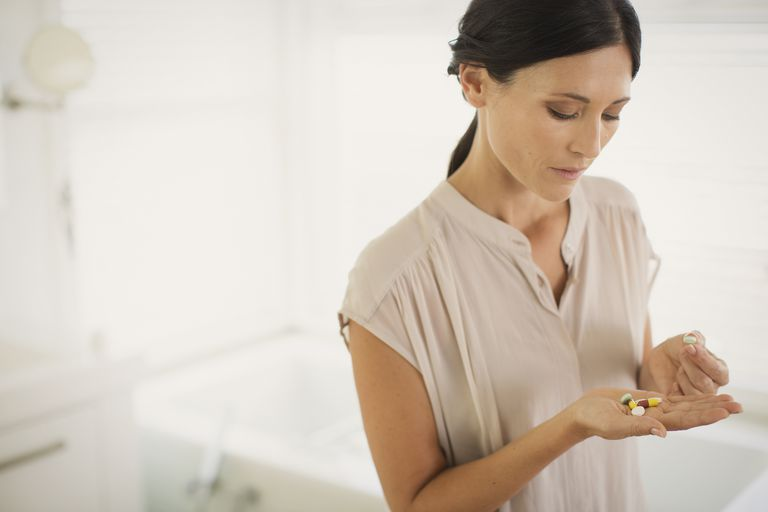 Woman looking at pills in hand