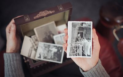 Hands of woman discovering a treasure chest full of photographs and holding an old black and white photograph of a smiling woman standing on a balcony in Rome in 1960s.
