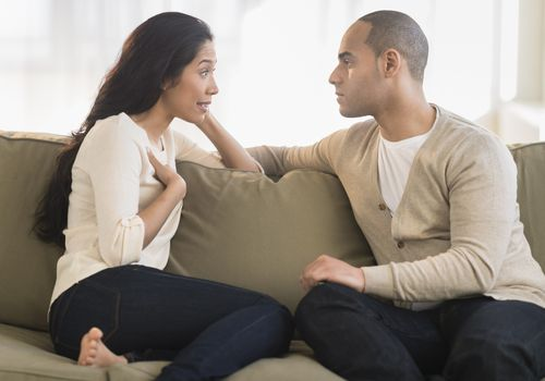 Young couple sitting on couch talking