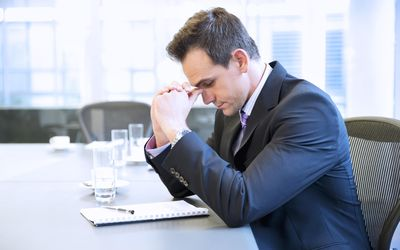 Businessman with head in hands in conference room.