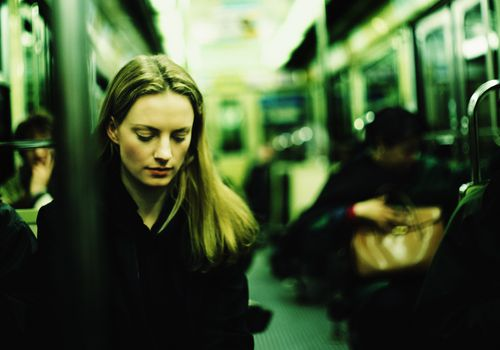 Woman looking at the ground on the subway train