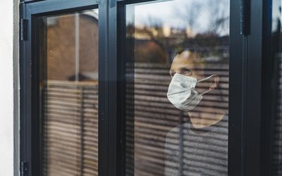 Man with mask looking out of window
