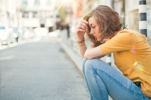 young woman sitting on the curb appears stressed