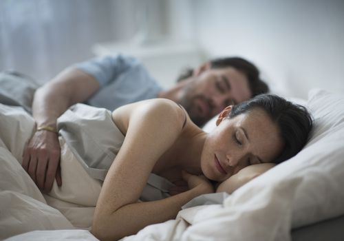 Couple sleeping together in bed at night