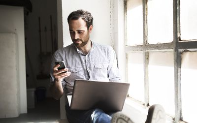 a man looking at his phone and computer on a windowsill