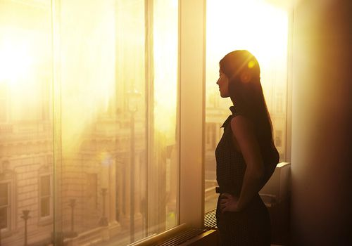 Woman standing in front of a large window filled with reflective sunlight